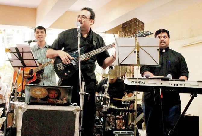 Fr Alban D'Souza (centre) seen leading the Ambassadors of Christ into music at a parish event in Mumbai.